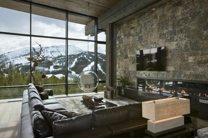 ein Wohnzimmer mit einer Glaswand und eine andere mit Wandverblender, Ledersofas und Kamin