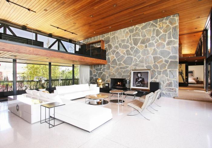 Wohnzimmer mit einer Glaswand, weiße Sofas, zwei Liegestühle, zwei Couchtische, eine Wand mit Wandverblender