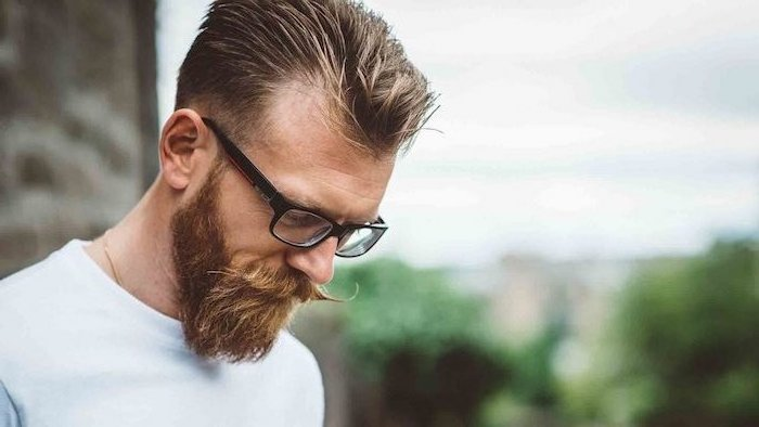 Dunkelblonde Haare mit Strähnen, Hipster Bart und Moustache, weiße Bluse, Brille mit schwarzem Rahmen
