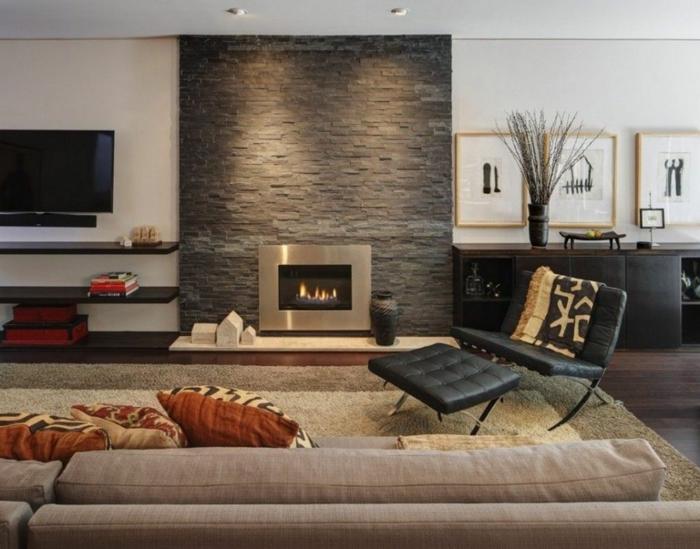 ein schöner Kamin mir Verblender Steinoptik, neben dem Fernseher, ein Sofa und schwarzer Liegestuhl