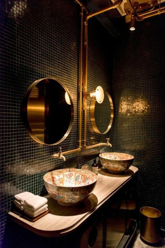 Waschtisch aus Holz mit ovalen Kanten, zwei runde Spiegel mit schlichtem Goldrahmen, zwei runde Becken mit Mosaikmotiven im ägyptischen Stil, zwei Wasserröhre mit Goldabdeckung, Bad mit schwarzen Wandfliesen