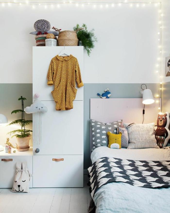 kleines Kinderzimmer mit zweifarbiger Wand, weißer Kleiderschran mit braunen Griffen, viele Plüschtiere, kleine Pflanze mit gespitzten Blättern, Kuscheldecke mit Print, Flechtkörbe zur Aufbewahrung