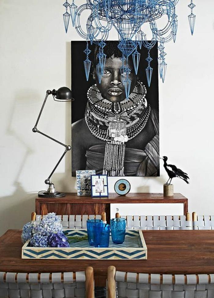 blauer Kronleuchter aus Edelstahl, massiver Esstisch aus Holz, Holzstühle mit weißen Rücklehnen
