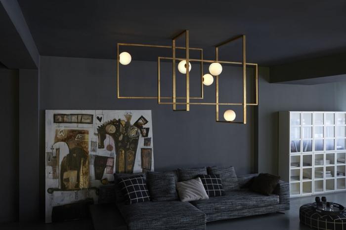 großer Kronleuchter aus Edelstahl mit Goldüberzung und runden Glühbirnen, Wohnzimmer schwarz gestalten - schwarze Wände und schwarze Decke, graue Eckcouch mit vielen Kissen