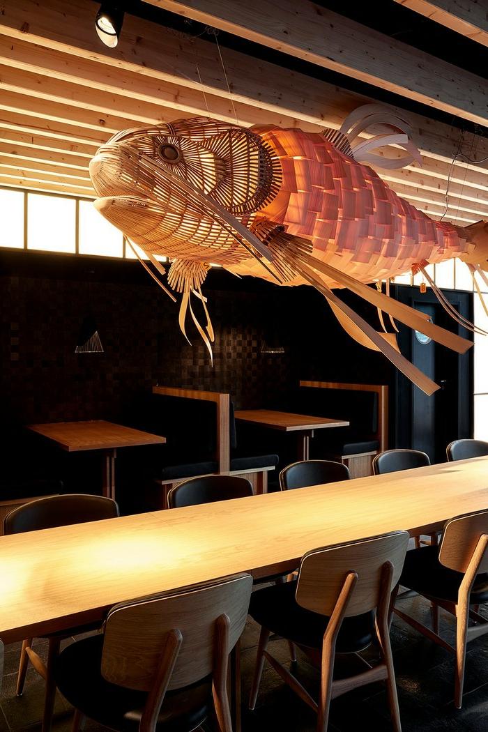 Kronleuchter aus Holz im asiatischen Stil, Lüster in der Form eines Fisches in einem asiatischen Restaurant mit Tischen aus Massivholz und Holzstühlen mit Ledersitzen