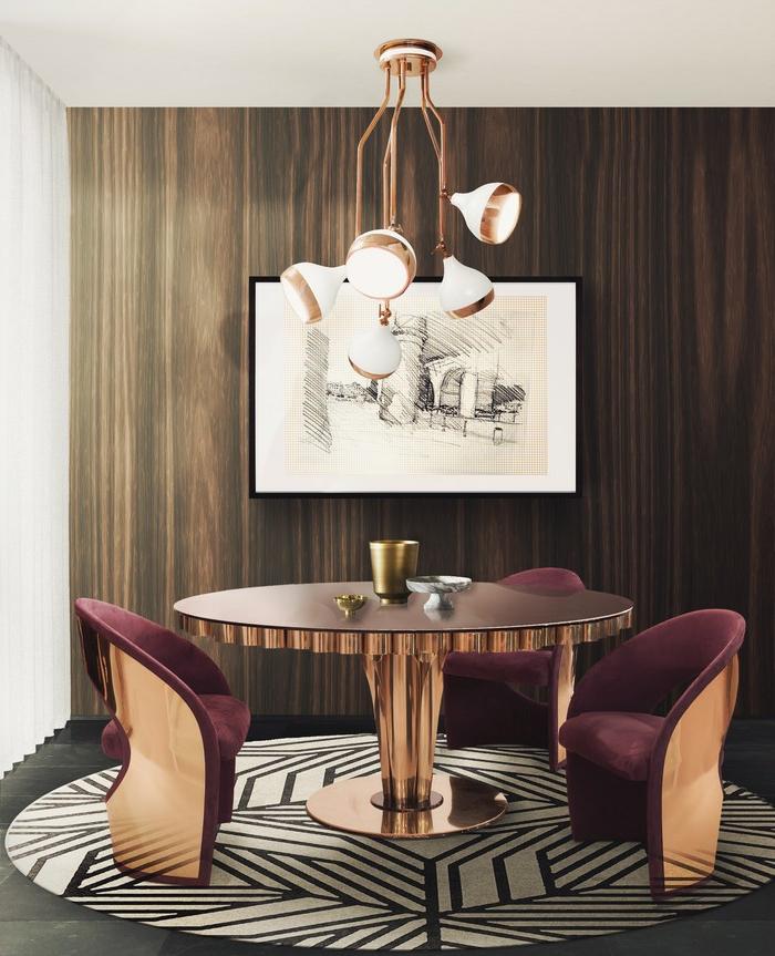 Kupfer-Kronleuchter für fünf Glühbirnen, Lüster mit Kupferüberzug, luxuriöses Esszimmer mit rundem Tisch aus Holz und Metall mit Kupferabdeckung, weinrote Polsterstühle mit Armlehnen, runder Teppich mit Muster