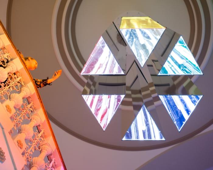 futuristische Lampenschirme aus gefärbtem Glas in der Form einer Pyramide, Treppen mit antiken Ornamenten, eine Frau macht Fotos mit ihrem Handy