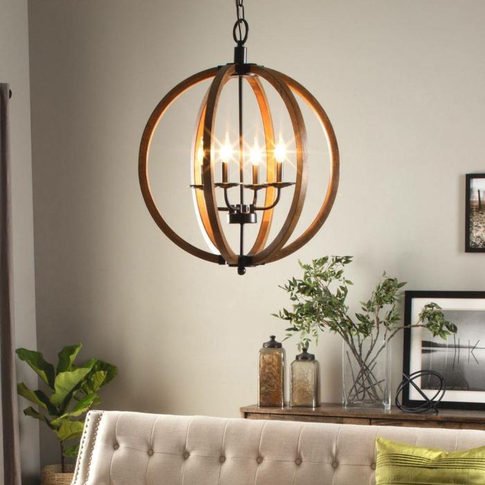runde Hängelamoe aus Holz mit vier kleinen Glühbirnen in der Form von Kerzen, Wohnzimmer mit weißer Couch mit dekorativen Metallkapseln und vielen grünen Pflanzen