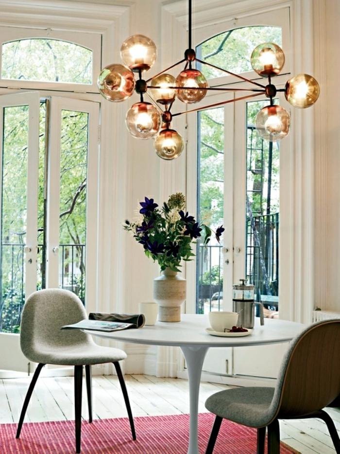 großer Leuchter mit neun Glaskugeln und drei Metallstäben, Esszimmer mit rundem weißen Tisch, Essstühle mit grauen Polstersitzen, roter Teppich mit hellen Streifen, zwei zweiflügeliche Glastüren die zur Terrasse fürhren
