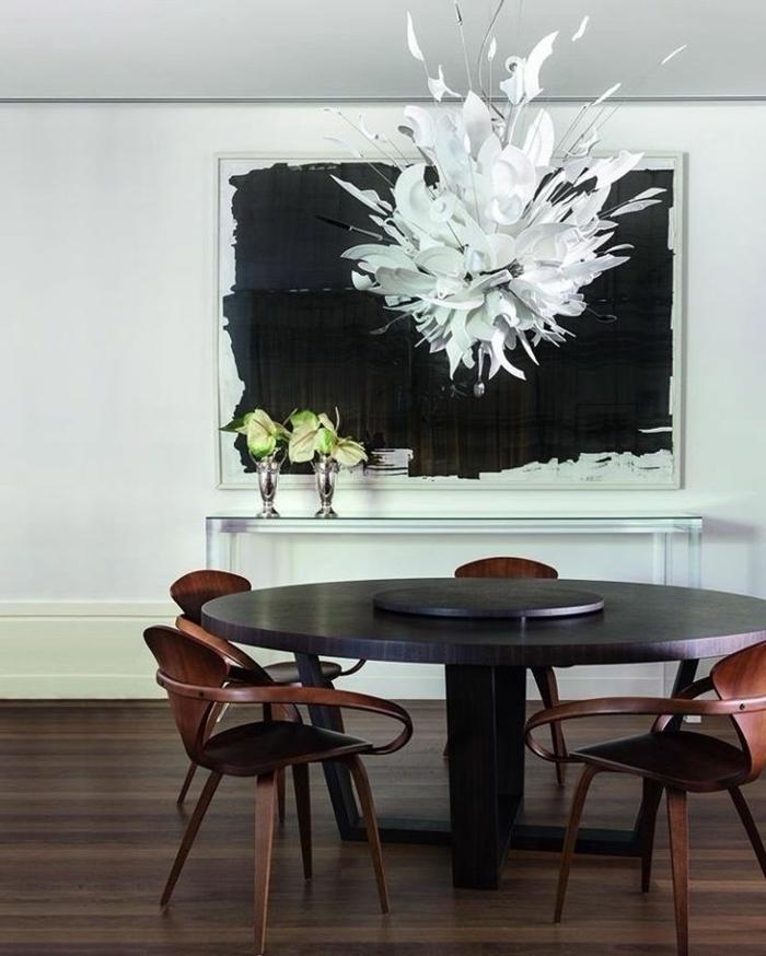 weißer Kronleuchter aus zerbrochenem Geschirr aus weißem Porzellan, schwarzer Esstisch in runder Form, braune Holzstühle mit minimalistischem Design