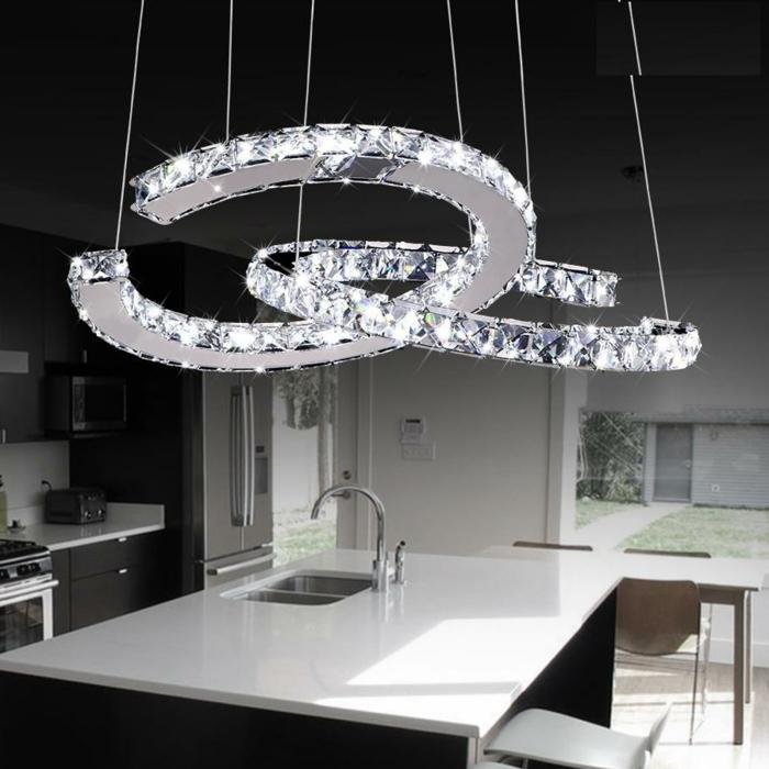 LED-Lampen in der Form von verflechteten Halbkreisen, schwarz-weiße Küche mit Kochinsel