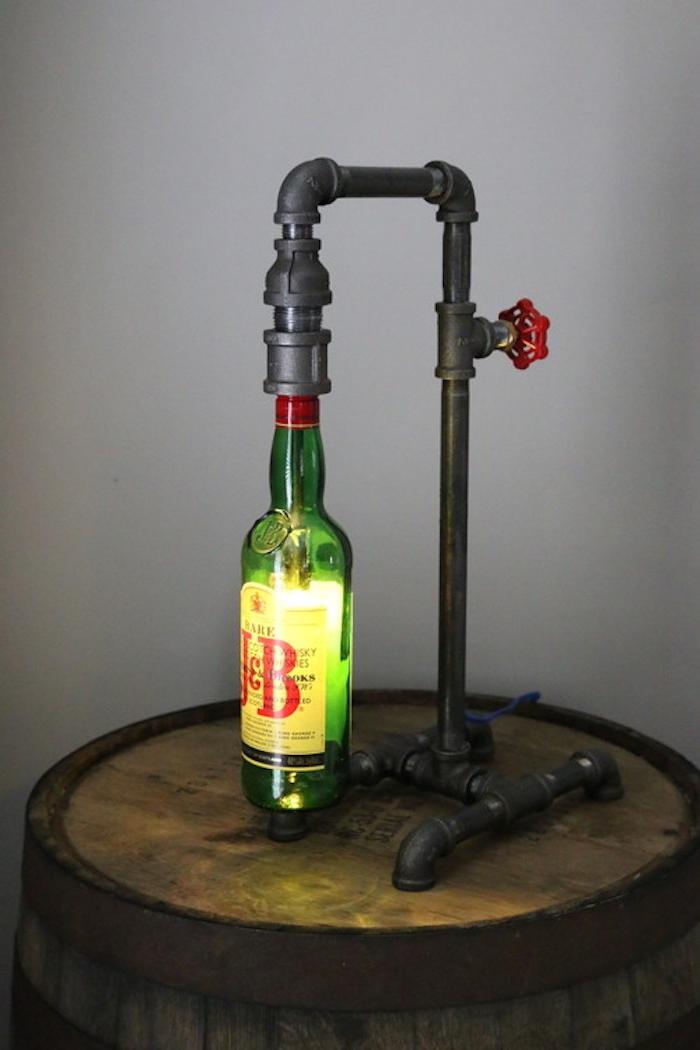 ein metallrohr und eine lampe mit einer grünen flasche