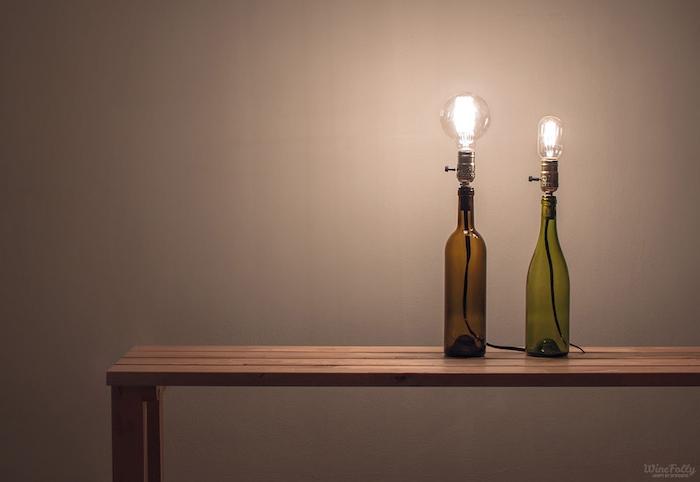 eine bank aus holz und zwei lampen aus grünen und braaunen glasflaschen und mit glühbirnen