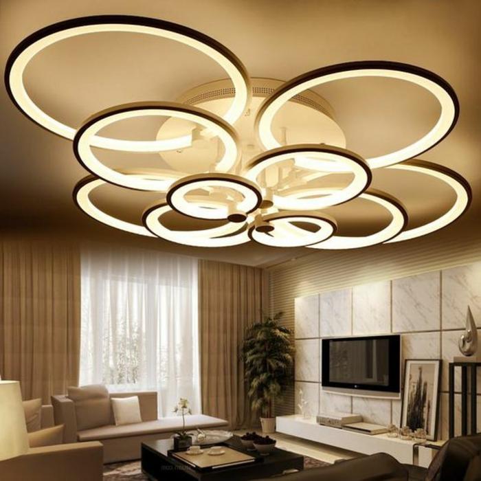 LED-Leuchte mit vielen Ringen aus Metall, Wohnzimmer beige gestalten - beige Couch mit vielen Couchkissen, lange Gardinen in Beige