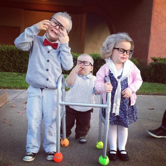 drei kleine Kinder verkleidet wie alte Menschen, kleine Jungen verkleidet wie zwei Opas in hellen Kleidern, kleines Mädchen verkleidet wie eine Oma