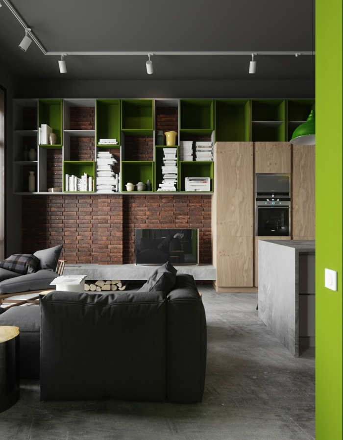 ein grünes Regalsystem an Verblender Steinopzik, bequeme Sessel im Vordergrund