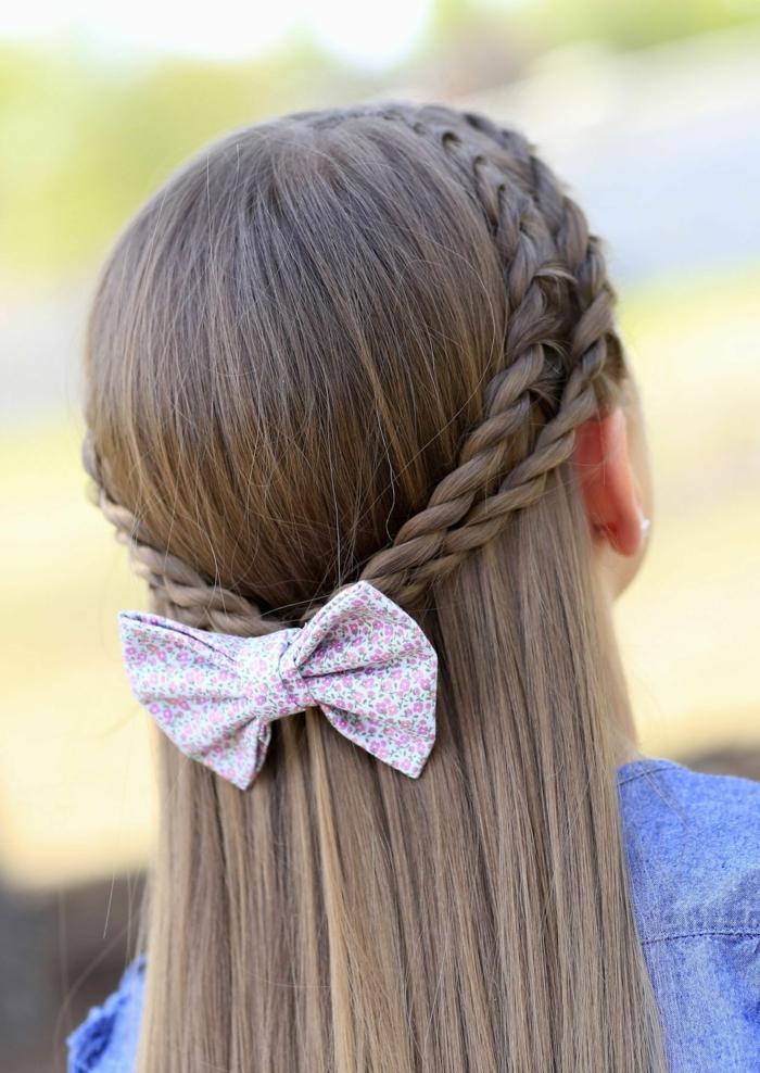 schicke Frisuren von einem kleinen Mädchen mit einer bunten Schleife