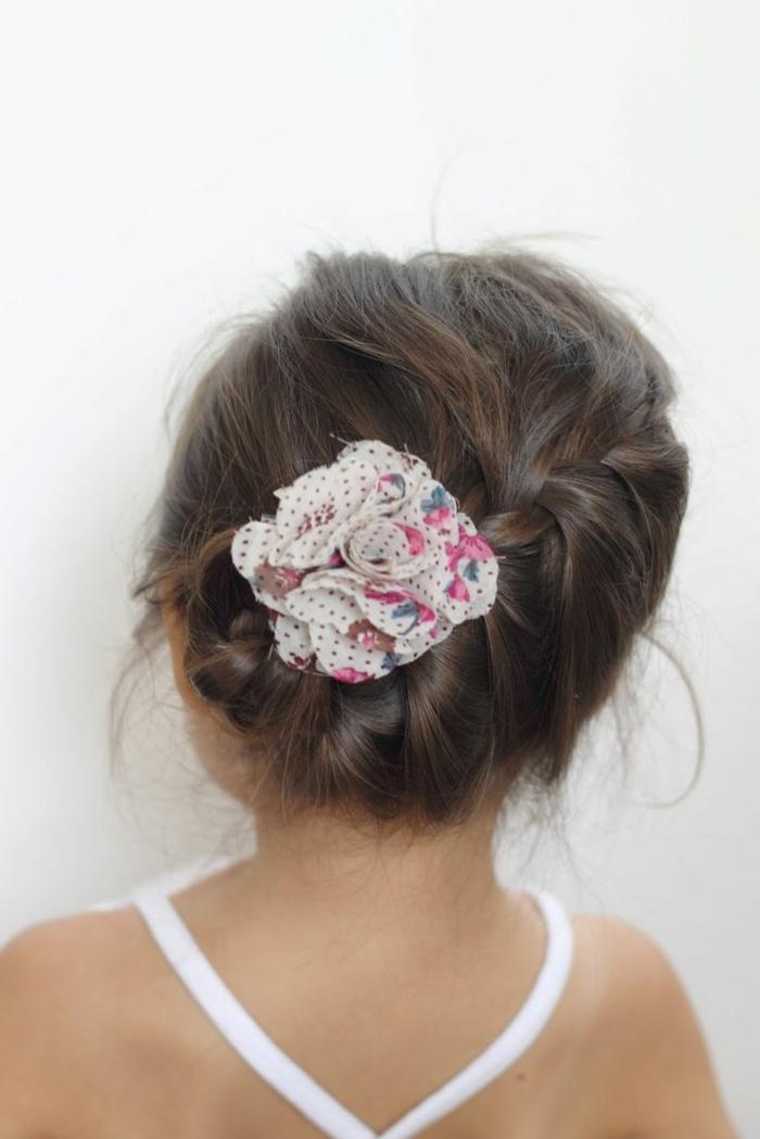 ein kleines Mädchen mit einer weißen Schleife mit Blumen Motive versehen