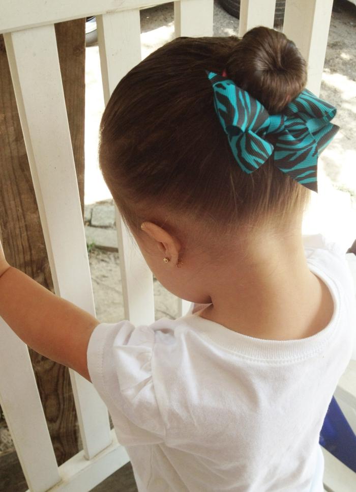 ein kleines Mädchen mit einer Hochsteckfrisur und einer blauen Schleife