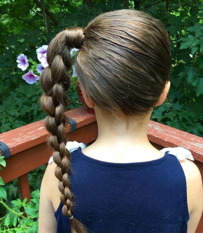 Frisur Mädchen - ein seitlicher Zopf von einem braunhaarigen Mädchen mit einem blauen Kleid