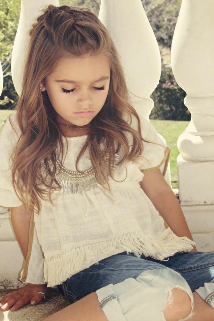 Frisuren Mädchen - eine weiße Bluse und moderne Jeans von einem kleinen Mädchen