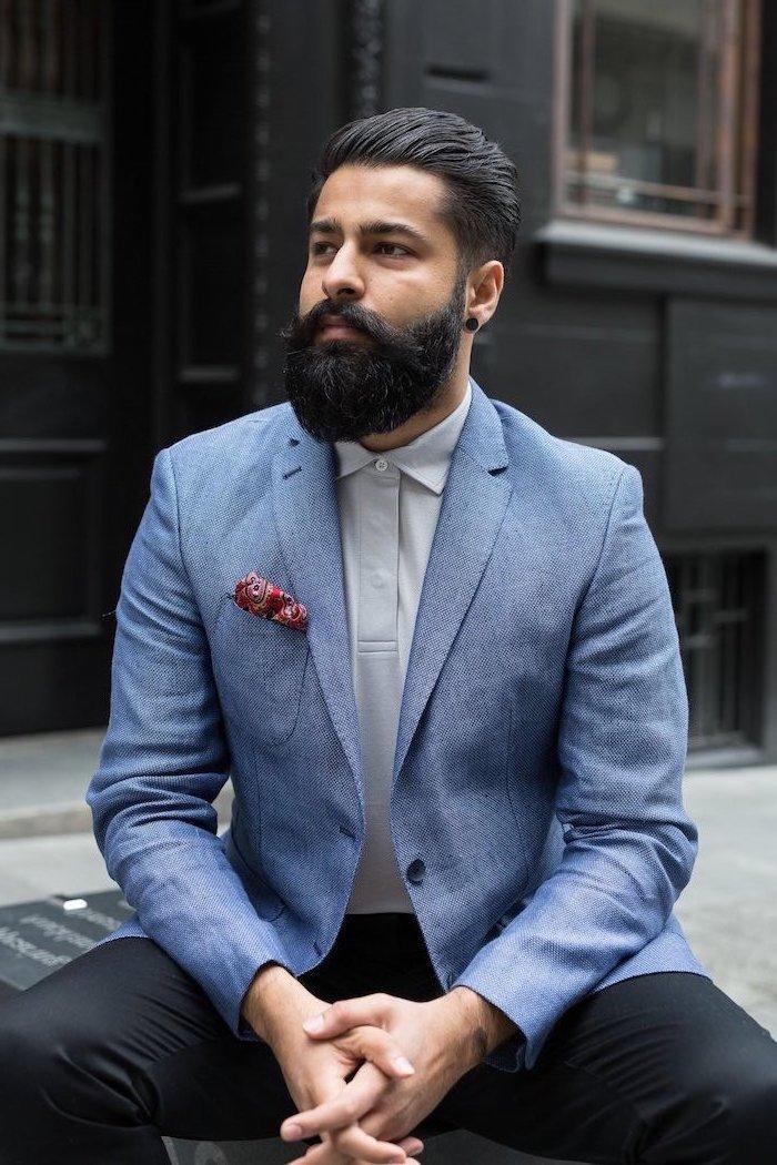Blauer Blazer, weißes Hemd und schwarze Hose, mittellange glatte Haare und Vollbart
