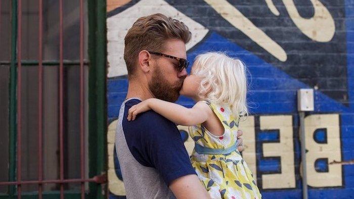 Vater und Tochter, kleines Mädchen mit platinblonden Haaren, Kleid mit Blumenmuster in fröhlichen Farben, der Herr hat Vollbart und Kurzhaarfrisur, trägt grau-blaues Shirt und Sonnenbrille