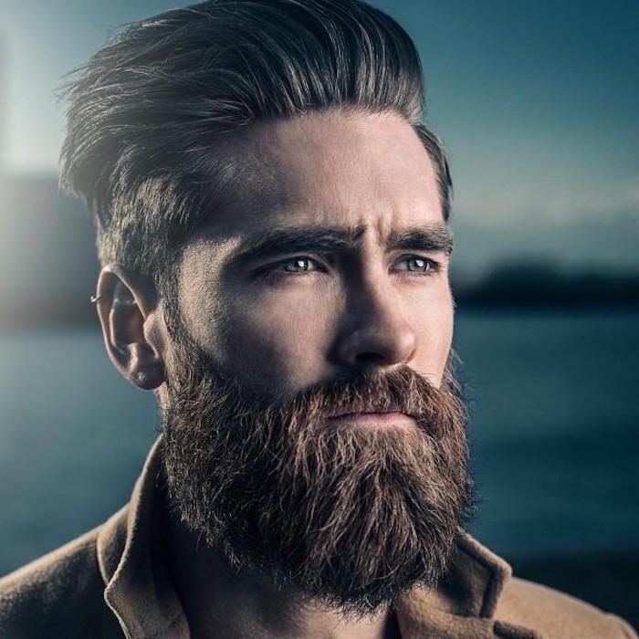 Herr mit kastanienbraunen glatten Haare und Vollbart, trägt braunen Mantel