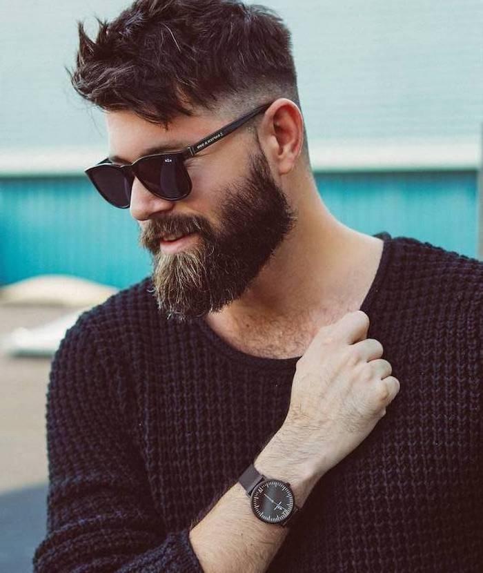 Kurzhaarfrisur und Hipster Bart, schwarzer Pullover mit langen Ärmeln, schwarze Sonnenbrille und Handuhr