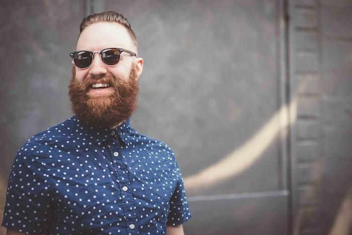 Vollbart und Kurzhaarfrisur, schwarze Sonnenbrille, dunkelblaues Hemd mit weißen Punkten