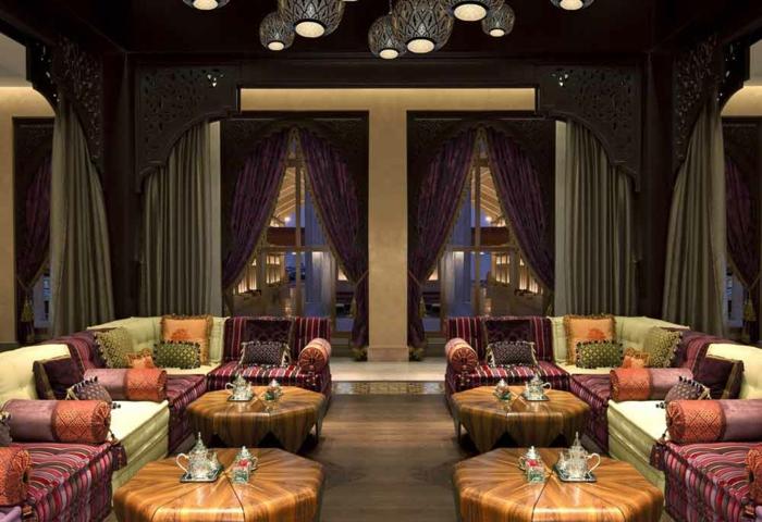 Cafe in Marokko mit vier Holztischen mit runder Form, gemütlichen Eckcouchen mit bunten Stoffen, kleine quadratische und runde Kissen, schwerfallende Vorhänge in Grau und Lila, runde Designer-Kronleuchter, Zimmerdecke mit Schnitzereien