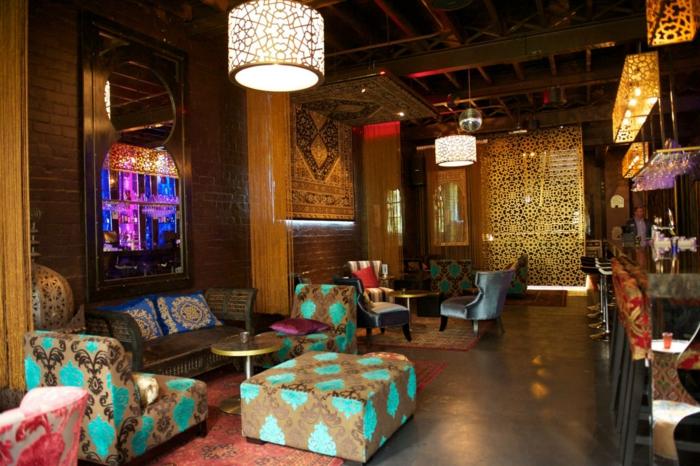 luxuriöse orientalische Einrichtung - Polstermöbel aus Musterstoffen, Musterteppich in Terrakkotta-Tönen, braun gefärbte Backsteinwände, riesiger Spiegel mit unregelmäßiger Form, eleganter Raumteiler mit Schnitzereien, Trennwand in Goldfarbe, Kronleuchter aus Glas