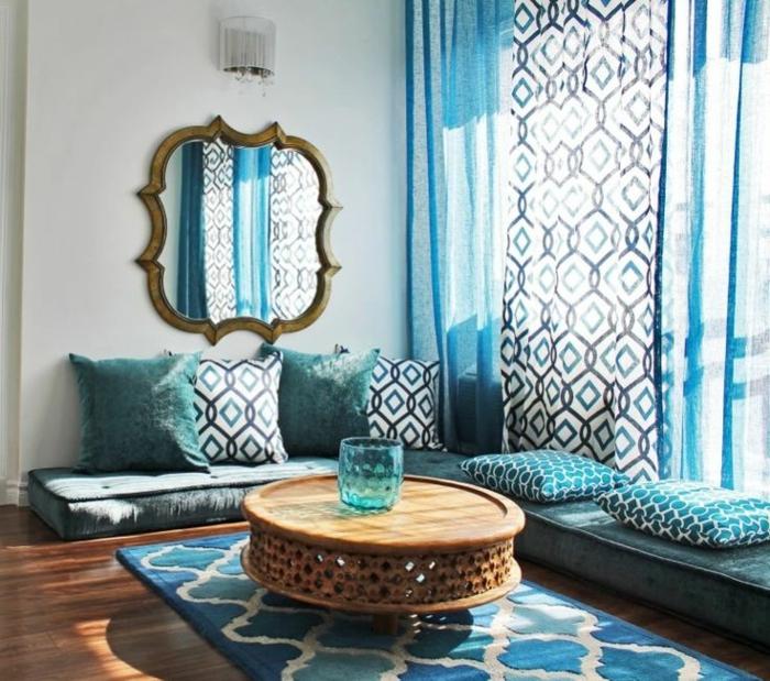 typische marokkanische Sitzecke in unterschiedlichen Blautönen und Weiß, weicher Musterteppich in drei Farben, großer Wandspiegel mit unregelmäßiger Form und ein vergoldetem Rahmen mit veraltetem Look, eine kleine Wandlampe darüber, niedriger runder Couchtisch aus Holz, blaue Glasvase mit runder Form, drei lange halbdurchsichtige Gardinen in Blau