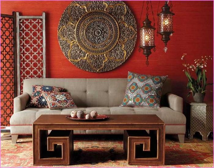 chinesische Sitzecke mit roten Wänden, runde Wanddeko aus Metall, Harmonika-Trennwand zur Dekoration, langer Holztisch mit untypischem Design, graue Couch mit Armlehnen, drei orientalische Couchkissen, kleiner Beistelltisch aus Metall mit einer Pflanze darauf, zwei Kronleuchter aus Glas, ei Haufen Bücher neben der Couch