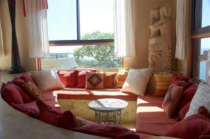 Kaffee-Ecke im Wohnzimmer, Couch in Terrakotta-Farbe mit ovaler Form, runder Tisch aus Metall mit vielen Ornamenten, zwei große Fenster mit kurzen weißen Gardinen, Statue aus Stein in der rechten Ecke des Zimmers