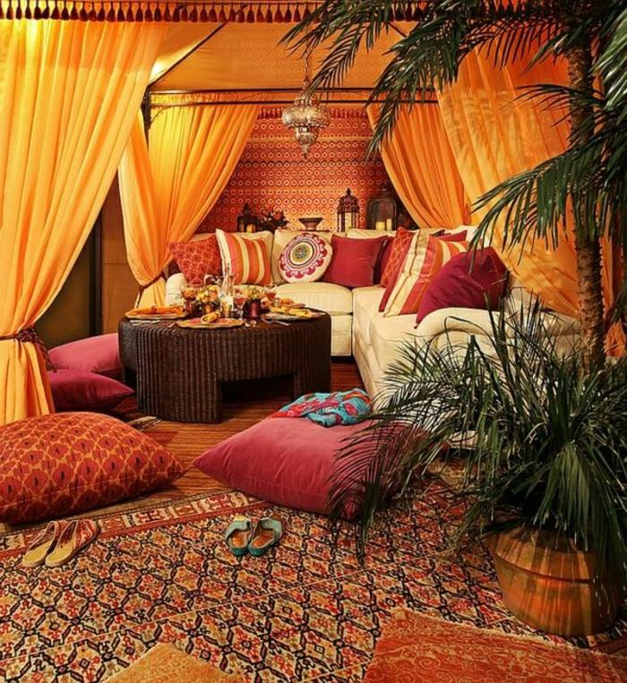 Sitzecke mit Baldahine mit orangen Vorhängen, weiße Eckcouch aus Leder, rote Couchkissen in untershiedlichen Größen, runder Flechttisch in Dunkelbraun, großer Musterteppich mit einem Blumentopf darauf, eine große und eine kleine Palme, Dekoelemente aus Metall