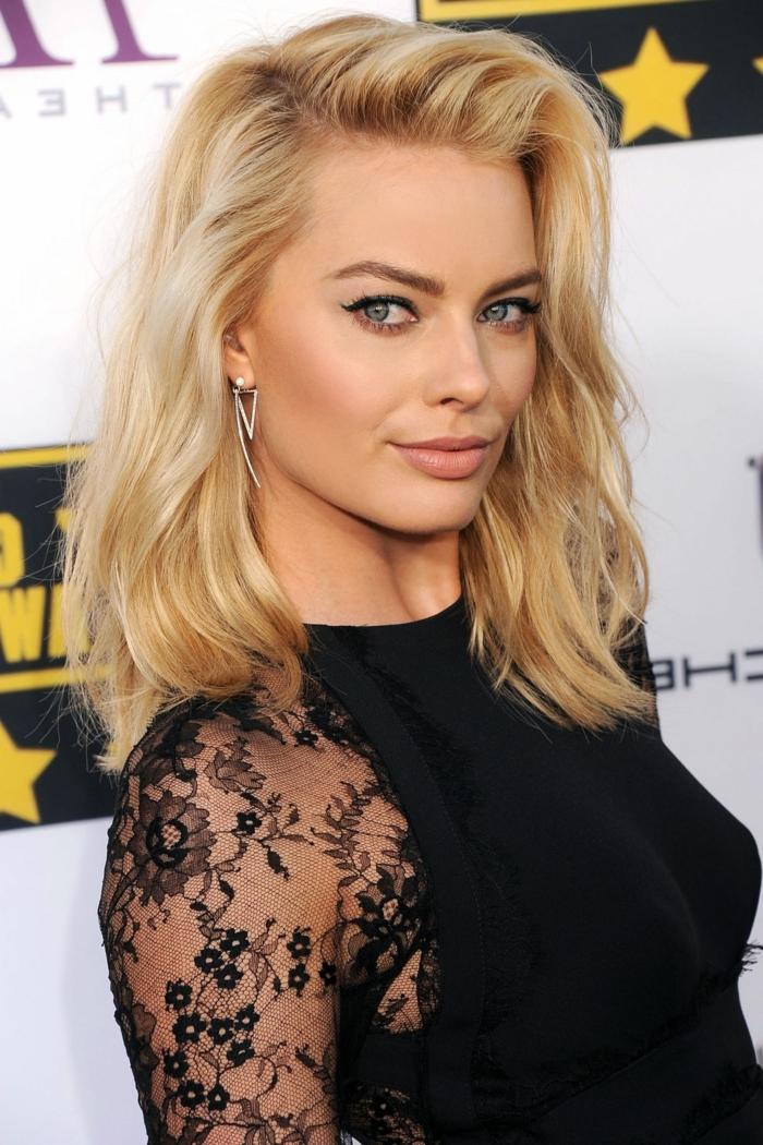 Frisur Schulterlang von einer blonden Schauspielerin, die silberne Ohrringe hat