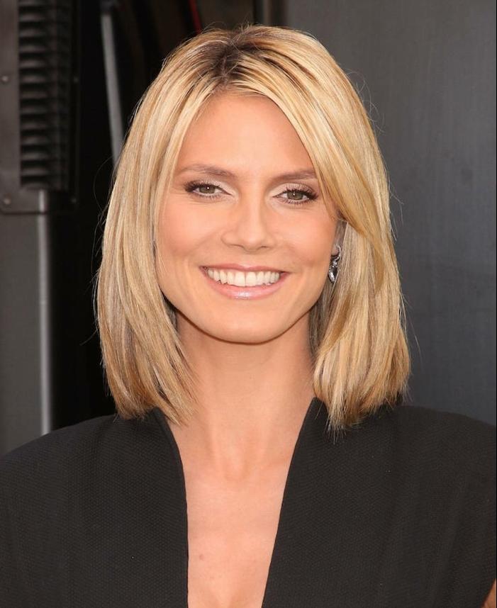 schulterlanges Haar, blondes Haar, schwarze Bluse, ausgefallene Ohrringe von einer Frau