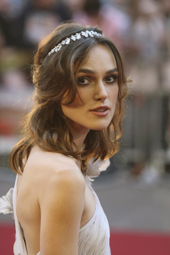 eine Schauspielerin mit schönen Perlenhaarschmuck in schulterlanges Haar