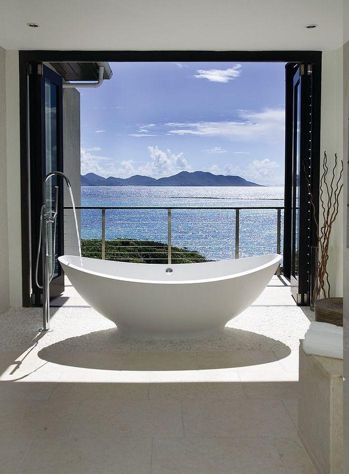 Meeres- und Gebirgeaussicht vom eigenen Bad, freistehende Badewanne vor dem Fenster, Terrasse mit zweiflügeliger Glastür, Deko aus Ikebanazweigen