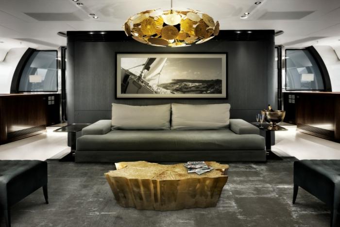 ovaler Kronleuchter mit goldenen Elementen, graues Wohnzimmer mit graauer Couch mit weißen Kissen, Designer-Couchtisch in Goldfarbe