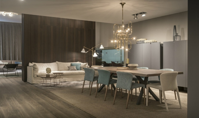 Esszimmer mit modernem Lüster, Massivtisch aus Holz, Polsterstühle in Weiß und Blas, weiße Couch mit zwei Couchtischen