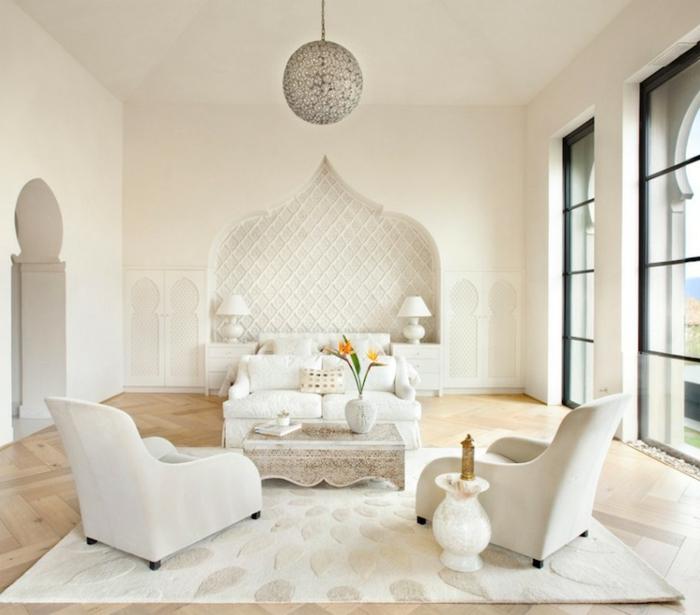 moderne orientalische Einrichtung, weiße Möbel mit schlichtem Design, zwei weiße Polstersessel, weißer Beistelltisch aus Marmot, weißer Teppich in quadratscher Form, niedriger Tisch mit weißer Marmortischplatte, ovale Blumenvase mit einer orangen Blume, kleine weiße Couch, Wandnische mit zwei Leselampen, zwei große Fenster bis zum Boden mit schwarzen Rahmen