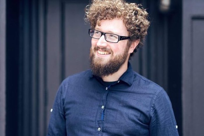 Herr mit natürlichen Locken und Vollbart, Brille mit schwarzem Rahmen, dunkelblaues Hemd