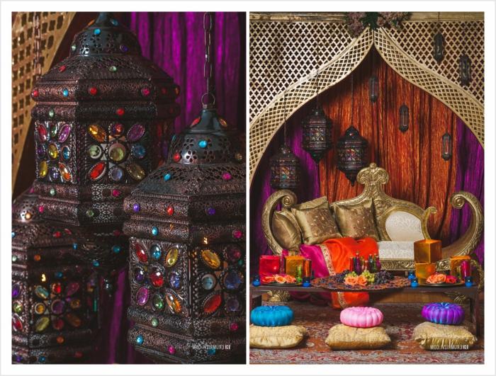 drei dekorative Leuchter aus Metall mit kleinen bunten Kristallen, Metallkronleuchter mit vielen Ornamenten, Fotocollage aus zwei Bildern, Designer-Couch mit Kissen in Goldfarbe, niedriger Glastisch mit reicher Dekoration, sechs Sitzkissen, runde Kissen in drei verschiedenen Farben, Wandverkleidung mit Schnitzerei, orange und lila Wandvorhänge