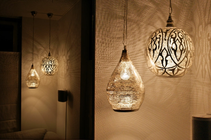 Zimmer mit weißen Wänden und weiißer Couch, vier Leuchter aus Metall mit interessanten Designs