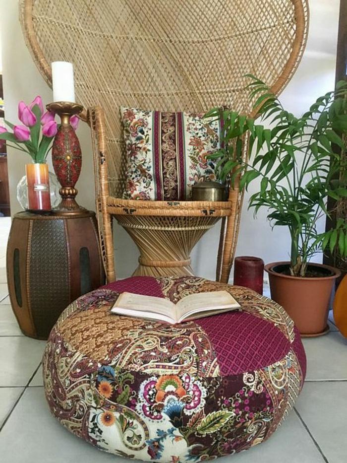 Leseecke mit Flechtstuhl, runde Sitzkissen aus Musterstoffen mit Applizierungen und ein offenes Buch darauf, drei Kerzen aus weißen und rotem Wachs, marokkanischer Kerzenleuchter aus Metall mit Inkrustationen, Beistelltisch mit ovaler Form, ein Strauß lila Tulpen, weiße Bodenfliesen