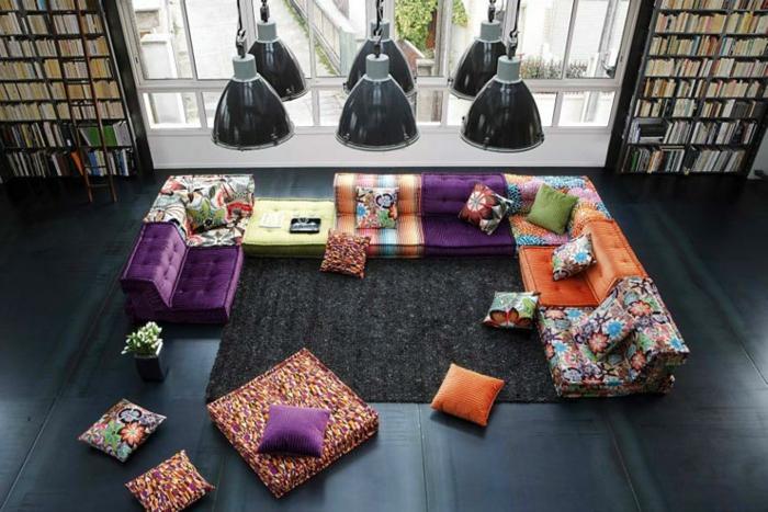 riesiges Wohnzimmer mit zwei großen Bücherregalend bis zur Decke, Bücherregal mit Leiter, große Polstercouch mit Stoffen mit unterschiedlichen Farbmustern, viele große und kleine farbige Sitz- und Couchkissen, schwarzer Boden mit schwarzem Teppich, sechs Kronleuchter im Industrialstil