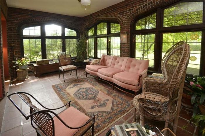 Zimmer mit orientalischen Möbeln in Naturfarben, aschenrosa Polstercouch mit Armlehnen, Musterteppich in Erdtönen, Haus mit Backsteinwänden, dre große Fenster