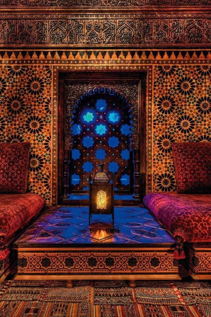 Zimmer mit Hauch vom Orient - Mustertapeten mit Kreisenmotiven, Wandverkleidung mit Schnitzerei, zwei Sessel mit gemütlichen Sesselkissen mit Troddeln, Tisch mit Zeichnungen, kleines Fenster in der Form eines Bogens